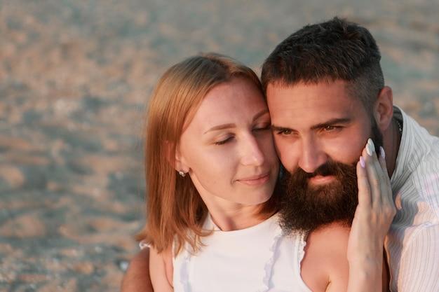 海のカップルの男と女は、ビーチの水の人々を愛しています