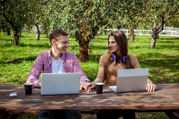 Парень и девушка сидят за деревянным столом в парке и работают на ноутбуках в наушниках. внештатная работа на открытом воздухе. работа вне офиса из-за пандемии covid 19