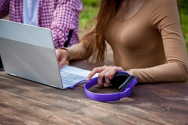 남자와 여자는 공원의 나무 테이블에 앉아 헤드폰을 끼고 노트북 작업을 합니다. 프리랜서는 야외에서 일합니다. 코로나19로 인해 사무실 밖에서 일하는