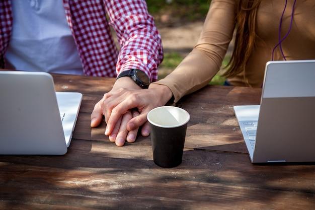 남자와 여자는 공원에 있는 나무 테이블에 앉아 헤드폰을 끼고 노트북 작업을 한다