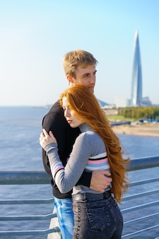 Парень и девушка вместе стоят на мосту через реку в солнечный день с видом на город