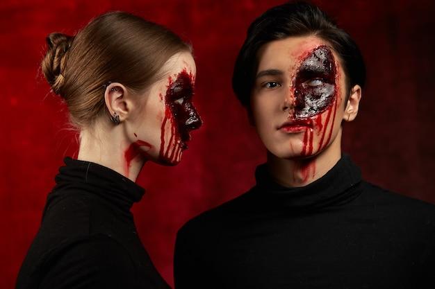 보라색 배경에 할로윈을 위해 얼굴에 피 묻은 화장을 한 남자와 여자