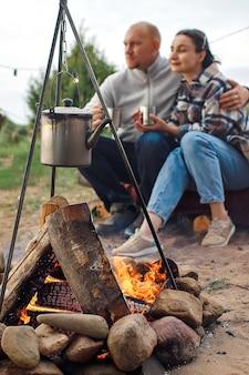 マグカップを手にした男と女が火事で体を温めている。