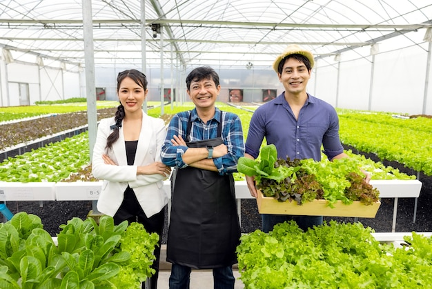 남자와 여자 농부는 행복과 기쁨을 배경으로 수경 채소 온실에서 자신의 창업 사업에 대한 자부심과 미소로 농장에 있습니다.