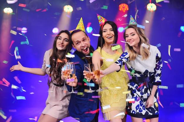Парень и три девушки радуются и празднуют вечеринку в ночном клубе