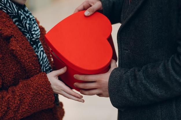 한 남자가 발렌타인 데이에 여자친구에게 하트 모양의 상자를 가까이서 줍니다. 쇼핑몰에서 젊은 부부.