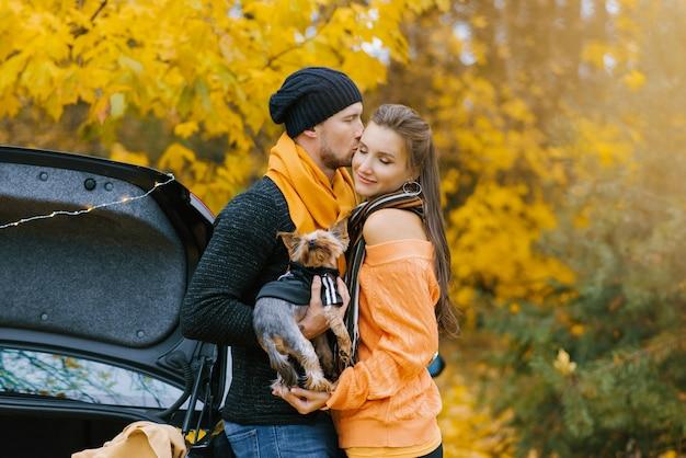 男はかわいい犬を腕に抱き、お気に入りの女の子にキスをします