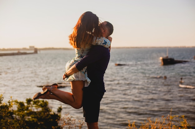 남자는 일몰 여름에 해변에서 그의 팔에 그의 여자 친구를 보유하고