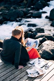Парень обнимает девушку-художницу, которая рисует акварелью картину в альбоме возле эхсараурфосса