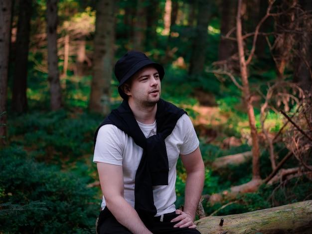 黒い帽子と白いtシャツを着た男が森の丸太に座って微笑む