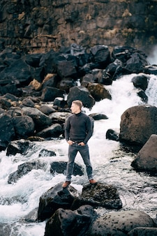 黒いニットのセーターを着た男が、エサラウルフォスの滝の近くの岩の上に立っています。エサラウ川国立公園