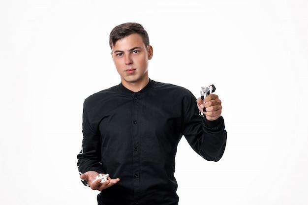 黒いシャツを着た男が、片手に壊れたタバコを持ち、もう片方にタバコのパックを持ってポーズをとります。タバコを放棄するという概念。喫煙は悪です