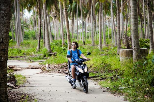 青いシャツを着た男がヤシの木に囲まれたジャングルでバイクに乗る