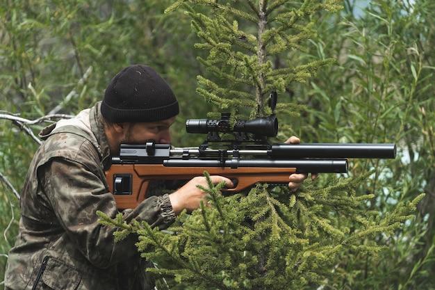 위장 카스툼을 입은 남자가 저격용 라이플을 들고 있습니다. 멧돼지 사냥. 저격수가 있는 무기를 들고 있는 남자