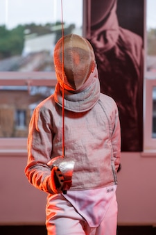 Парень в фехтовальном костюме с мечом в руке, неоновый свет. юная модель тренирует и тренирует движение, действие. спорт, молодость, здоровый образ жизни.