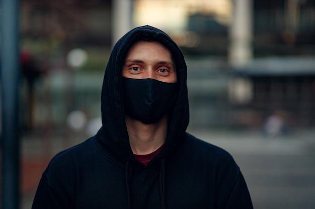 의료용 마스크를 쓴 남자가 거리를 걷고 있습니다. 코로나바이러스와 전염병으로부터 건강과 안전 생활의 개념. 스테디캠으로 촬영. covid-19 또는 코로나바이러스 2019 개념.
