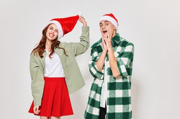 격자 무늬 셔츠에있는 남자와 밝은 배경에 크리스마스 모자에있는 여자. 고품질 사진
