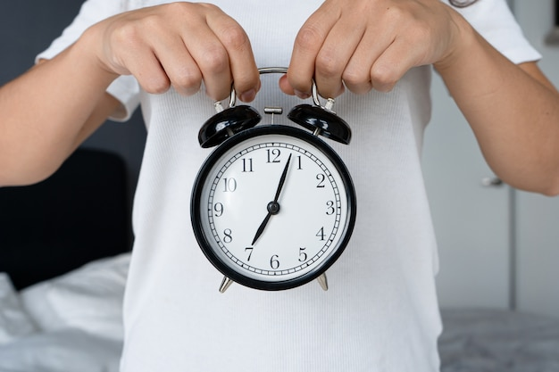 Парень в белой футболке держит стильный черный будильник с колокольчиком. на будильнике начало восьмое. время вставать.