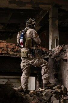 アメリカの軍服を着た男が部屋の山にある老朽化した建物に立っているエアガン