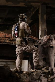 Парень в американской военной форме стоит в полуразрушенном здании на груде комнат страйкбол