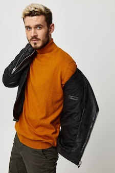 Парень в оранжевом свитере и кожаной куртке держит руку возле лица на светлом фоне. фото высокого качества