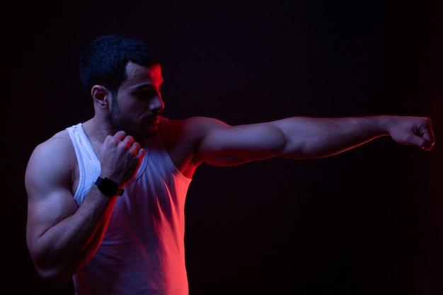 Парень в боксерской стойке в темной комнате