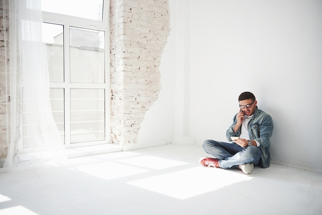 カジュアルな服装の男が家の空いているアパートに座って電話をかけている。おそらく彼は奪われたか、彼らはすべての財産を借金のために奪ったのでしょう。