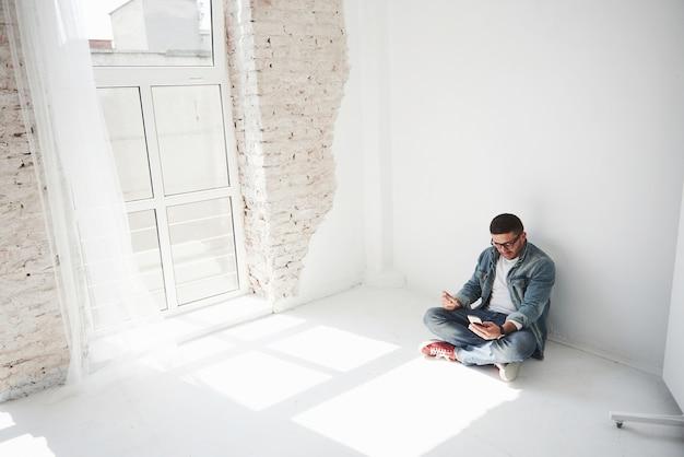 カジュアルな服装の男が、クレジットカードを持って電話をかけている空のアパートに家に座っています。たぶん彼は新しい居住者で、まだ家具を購入していません。