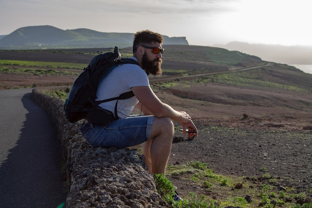 Парень в летней одежде сидит на каменном заборе и смотрит вдаль. мирадор-дель-рио, лансароте, испания.