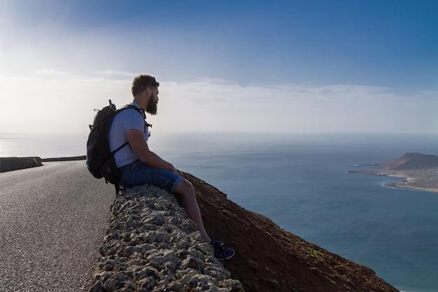 Парень в летней одежде сидит на каменном заборе и смотрит на ближайший остров в океане. мирадор-дель-рио, лансароте, испания.