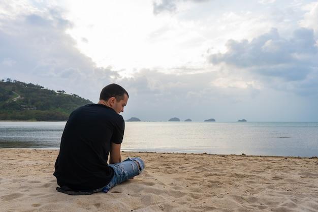 Парень сидит на песчаном пляже и смотрит на воду. наслаждается красивыми пейзажами природы.