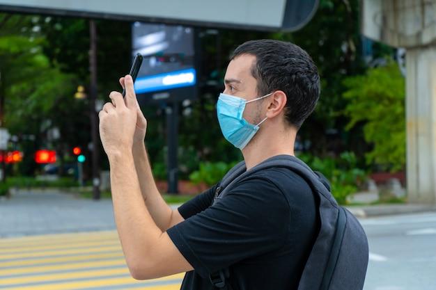 Парень турист с рюкзаком на спине и хирургической маской на лице, фотографирует здания на городской улице. коронавирус пандемия. последствия для туризма.