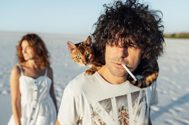 Парень с кошкой на шее курит сигарету. девушка стоит на заднем плане