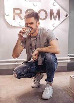 手にコーヒーを持った男がカメラを見る