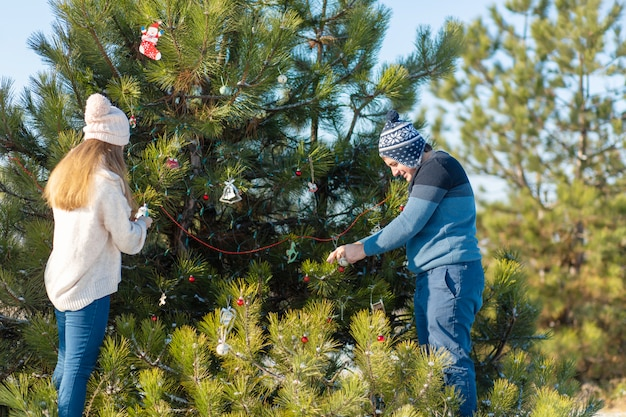 Парень с девушкой украшают зеленую елку на улице зимой в лесу декоративными игрушками и гирляндами. елочные украшения