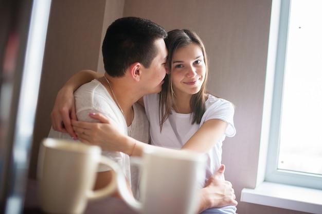 Парень с девушкой пьют кофе у окна