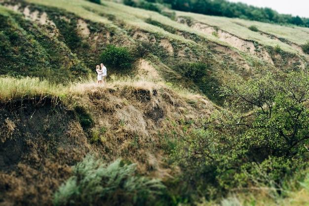 地球の侵食の緑の峡谷の背景に明るい服を着た女の子と男