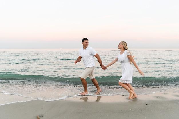 夏服を着た女の子と一緒に海を歩いている男。海の近くの日のロマンチックな夕日で夫と妻。恋人たちはビーチに沿って走ります。