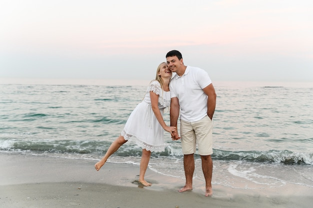 夏服を着た女の子と一緒に海を歩いている男。海の近くの日のロマンチックな夕日で夫と妻。
