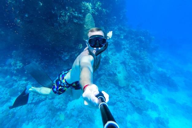 Парень в маске и трубке ныряет в голубую воду красного моря и фотографирует себя