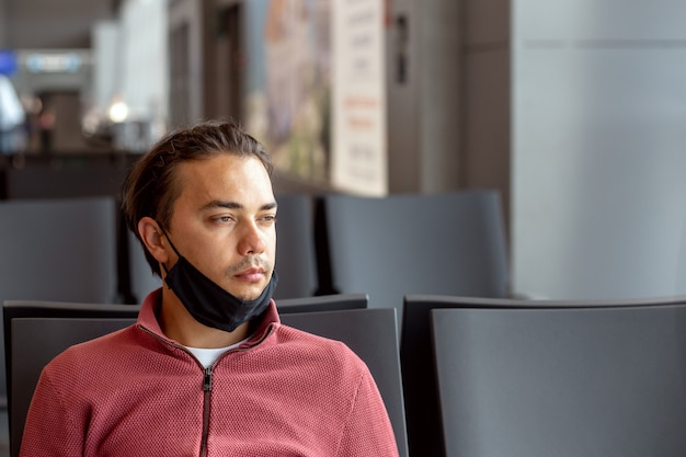 Парень с защитной черной медицинской маской на лице в аэропорту ждет рейса