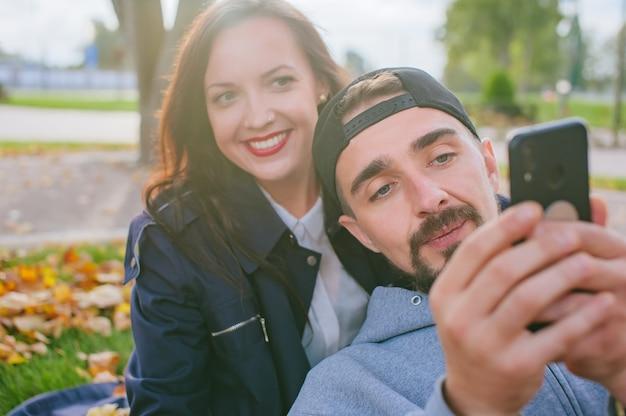 Парень со смартфоном в руках сидит осенью в листве со своей любимой счастливой девушкой.