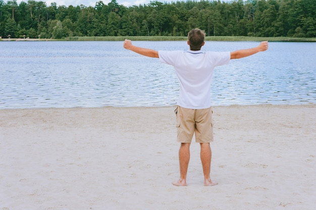 ビーチと森の背景に手を伸ばした男。