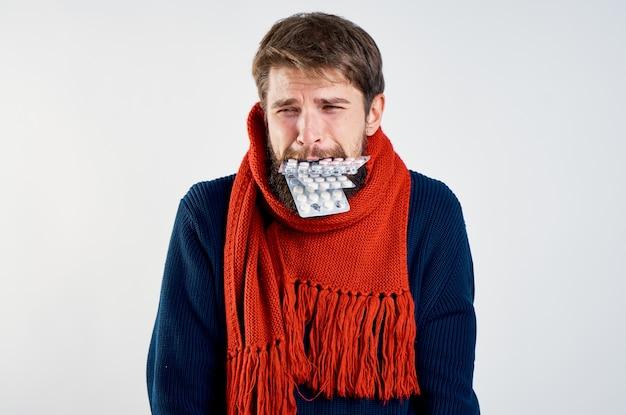 Парень с таблетками во рту и в красном шарфе