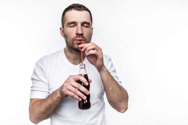 숏컷을 한 남자가 빨대를 통해 병에서 콜라를 마시고 있습니다. 이 남자는 패스트 푸드를 먹고 단 음료를 마시는 것을 좋아합니다. 흰색 배경에 고립