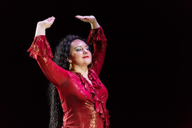 巻き毛の黒い髪のジプシーの女性は、黒い背景に赤いドレスを着て踊ります。横の写真