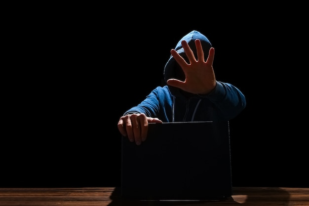 Хакер с ноутбуком сидит за столом и абстрактным двоичным кодом. виртуальные программы угроз деловой жизни.