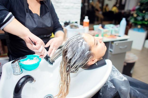 미용사는 미용실에서 고객의 머리카락에 크림이나 마스크를 바릅니다. 여자는 이발소에서 그녀의 머리를 염색
