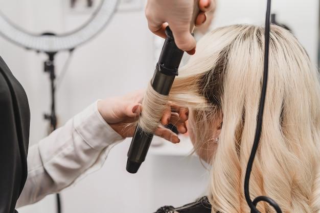 Парикмахер делает блондинку в салоне красоты. сделать локоны плойкой