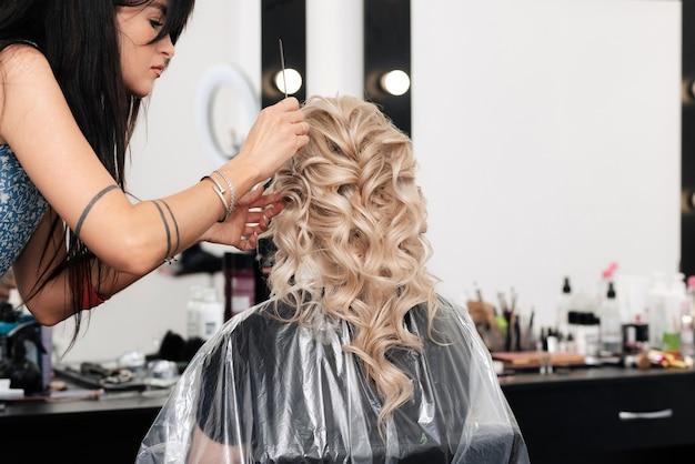 Девушка-парикмахер укладывает локоны в прическу в салоне красоты